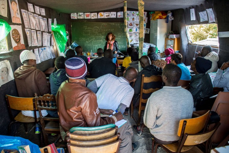 """Migrants attend a French class at a makeshift school set up in the """"New Jungle"""" in Calais, northern France, on September 10, 2015, where more than 3,500 people have settled temporarily. (PHILIPPE HUGUEN/AFP/Getty Images)"""