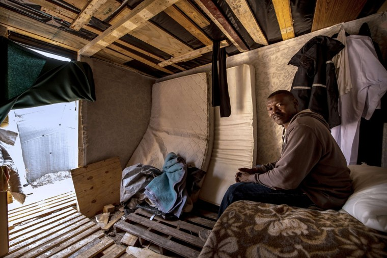 """Abdel Hafez Seddig, a 33-year-old migrant from Sudan, takes cover from the rain inside a hut at a makeshift camp known as the """"New Jungle"""" in Calais in northern France on September 14, 2015. Under an agreement between the British and French governments, British border controls are carried out on the French side of the Channel Tunnel, making Calais the focal point of attempts by migrants to cross into England. Thousands of migrants over the summer attempted to cross the Channel Tunnel between Britain and France, which later stepped up border controls. (PHILIPPE HUGUEN/AFP/Getty Images)"""