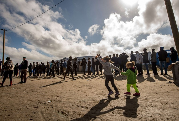 """Migrants wait to get food at a site dubbed the """"New Jungle,"""" where some 3,000 people have set up camp -- most seeking desperately to get to England, in Calais on September 19, 2015. The slum-like migrant camp sprung up after the closure of notorious Red Cross camp Sangatte in 2002, which had become overcrowded and prone to violent riots. However migrants and refugees have kept coming and the """"New Jungle"""" has swelled along with the numbers of those making often deadly attempts to smuggle themselves across the Channel. (PHILIPPE HUGUEN/AFP/Getty Images)"""