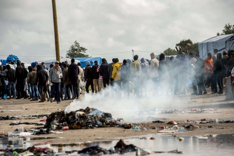 """Migrants wait to get food at a site dubbed the """"New Jungle"""", where some 3,000 people have set up camp -- most seeking desperately to get to England, in Calais on September 19, 2015. (PHILIPPE HUGUEN/AFP/Getty Images)"""