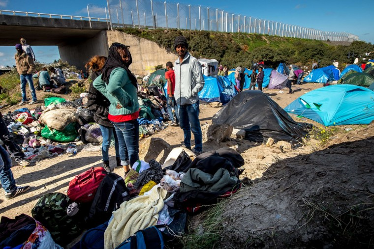 """Migrants stand near tents at a site dubbed the """"New Jungle,"""" where some 3,000 people have set up camp -- most seeking desperately to get to England, in Calais on September 19, 2015. (PHILIPPE HUGUEN/AFP/Getty Images)"""