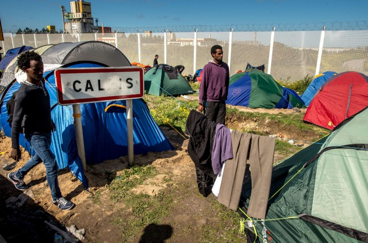 """Migrants camp at a site dubbed the """"New Jungle,"""" where some 3,000 people have set up camp -- most seeking desperately to get to England, in Calais. The slum-like migrant camp sprung up after the closure of notorious Red Cross camp Sangatte in 2002, which had become overcrowded and prone to violent riots. However migrants and refugees have kept coming and the """"New Jungle"""" has swelled along with the numbers of those making often deadly attempts to smuggle themselves across the Channel. (PHILIPPE HUGUEN/AFP/Getty Images)"""
