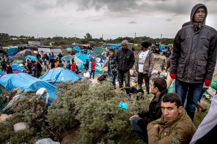 """People stand at a site dubbed the """"New Jungle,"""" where some 3,000 people have set up camp -- most seeking desperately to get to England. (PHILIPPE HUGUEN/AFP/Getty Images)"""