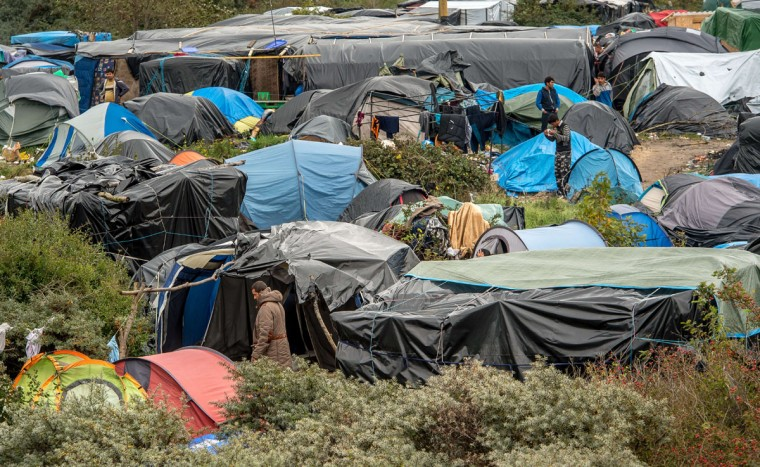 """People stand next to a site dubbed the """"New Jungle,"""" where some 3,000 people have set up camp -- most seeking desperately to get to England, in Calais on October 7, 2015. (PHILIPPE HUGUEN/AFP/Getty Images)"""