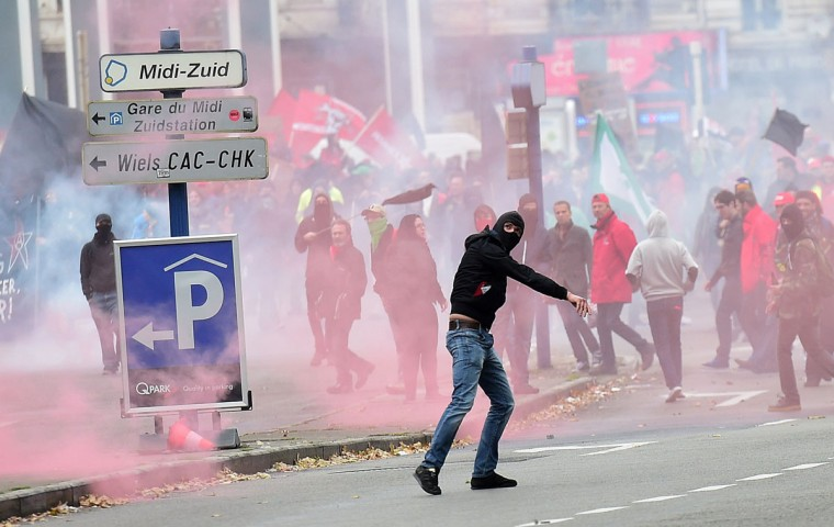 A demonstrator hurls a missile towards police as clashes erupted at a march against government reforms and cost-cutting measures in Brussels on October 7, 2015. Tens of thousands of Belgian protesters took to the streets of Brussels to rally against austerity measures introduced by the government of Prime Minister Charles Michel, police and trade unions said. (AFP Photo/Emmanuel Dunand)