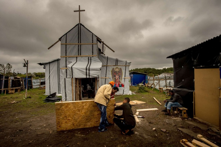 """A picture taken in Calais on October 7, 2015 shows a makeshift church at a site dubbed the """"New Jungle,"""" where some 3,000 people have set up camp -- most seeking desperately to get to England. (PHILIPPE HUGUEN/AFP/Getty Images)"""