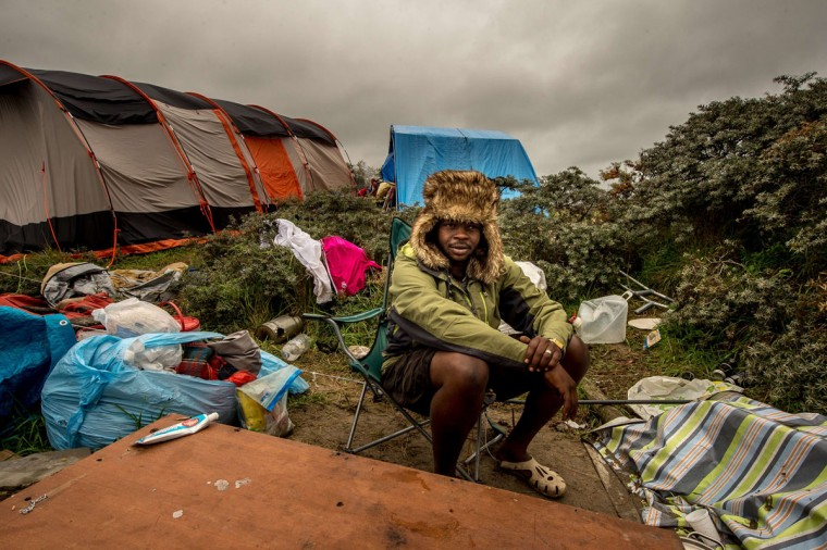 """A picture taken in Calais on October 7, 2015 shows a man sitting at a site dubbed the """"New Jungle,"""" where some 3,000 people have set up camp -- most seeking desperately to get to England. (PHILIPPE HUGUEN/AFP/Getty Images)"""