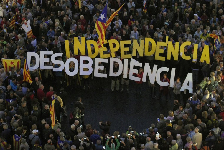 "People gather with two banners that read "" Indenpendece"" and ""disobedience"" during a protest outside Barcelona's City Council on October 13, 2015 in support of Catalonia's regional government president and leader of the Catalan Democratic Convergence (CDC) Artur Mas, the Catalan Minister of Education Irene Rigau and the former Catalan vice-president of Catalonia's regional government Joana Ortega who are charged with civil disobedience and misuse of public funds for holding a non-binding ballot in November 2014 in which Catalans were asked to vote on whether their region should remain part of Spain. Spanish judges today started questioning Catalan officials charged with breaking the law by holding a vote last year on their contested drive for independence from Spain. (AFP Photo/Lluis Gene)"