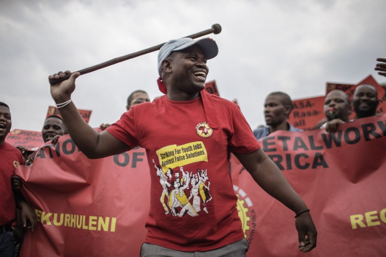 A man holds a batton as National Union of Metalworkers of South Africa (NUMSA) and anti-corruption activists gather as thousands of protesters from various South African political and civil society groups and trade unions march through the streets of Johannesburg, South Africa, on October 14, 2015 to protest against rampant corruption. Several thousand demonstrators marched through Johannesburg to protest against government corruption as public anger builds over South Africa's weakening economy. The rally was led by the National Union of Metal Workers of South Africa (NUMSA), which has become a powerful voice of opposition to President Jacob Zuma and the ruling Africa National Congress (ANC) party. (AFP Photo/Gianluigi Guercia)
