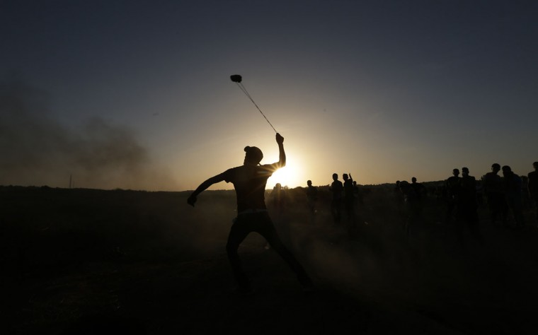 A masked Palestinian protester hurls a stone towards Israeli troops during clashes near a border fence between Israel and the Gaza Strip n October 14, 2015 east of Bureij in central Gaza. The outbreak of violence between Palestinians and Israeli forces in recent weeks has worsened in October, raising fears of a third intifada, or uprising. (AFP Photo/Mahmud Hams)
