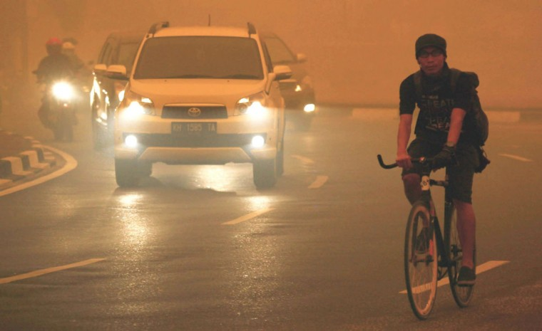 Motorists turn on their vehicle head lamps during the day in Palangkaraya city, one of worst-hit by haze in central Kalimantan province, on October 21, 2015. Indonesian forest and agricultural fires cloaking Southeast Asia in acrid haze are spewing more greenhouse gases into the atmosphere each day than all US economic activity, according to an environmental watchdog. (WISANGGENI/AFP/Getty Images)