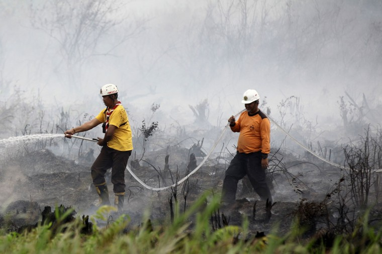 Indonesian men put out a fire in Ogan Ilir, southern Sumatra on October 22, 2015. Dense haze from Indonesian forest fires has caused some of the worst pollution in southern Thailand for a decade, officials said October 22, cancelling flights in an area popular with tourists. (ABDUL QODIR/AFP/Getty Images)