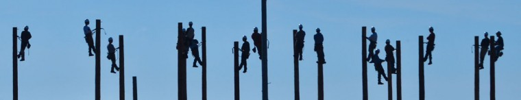 Students in a lineman class hold their positions atop poles during a climbing session at Calhoun Community College in Decatur, Ala., Tuesday, Oct. 6, 2015. The prospective lineman were learning pole climbing skills using belts and strap on climbing spikes. (Gary Cosby Jr./The Decatur Dailyvia AP)