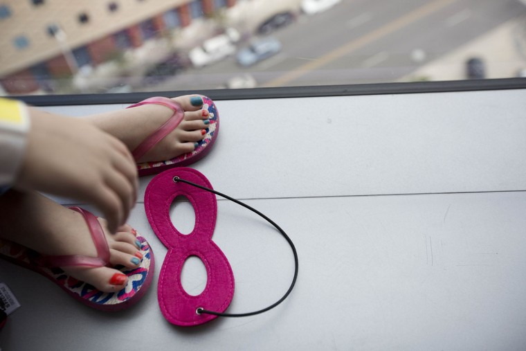 Miley Eady, 7, of Birmingham, lays down her super hero mask while she waits for the super hero window washers at the Benjamin Russell Hospital for Children, Wednesday, Oct. 7, 2015, in Birmingham, Ala. (AP Photo/Brynn Anderson)
