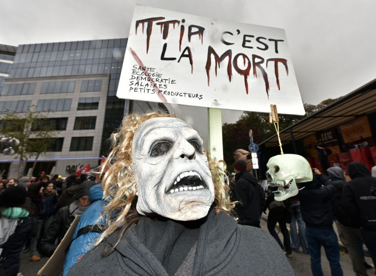 "A protestor with a mask demonstrates against the free trade agreement TTIP (Transatlantic Trade and Investment Partnership) during an EU summit in Brussels, Belgium on Thursday, Oct. 15, 2015. His banner reads ""TTIP is the dead"". European Union heads of state meet to discuss, among other issues, the current migration crisis. (AP Photo/Martin Meissner)"