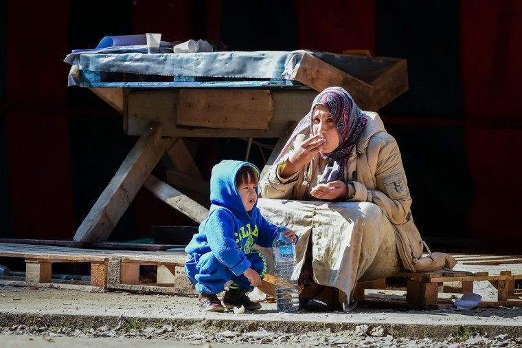 A woman and child eat in front of a deserted food stand in a tent camp for refugees in Brussels on Thursday, Oct. 1, 2015. Civil organizations, city services and NGO's dismantled the tent camp in which several 100 refugees have lived for some weeks as they apply for asylum in Belgium, but volunteers have decided it was no longer suitable for refugees to live outside and have found local families to host the migrant families.(AP Photo/Geert Vanden Wijngaert)