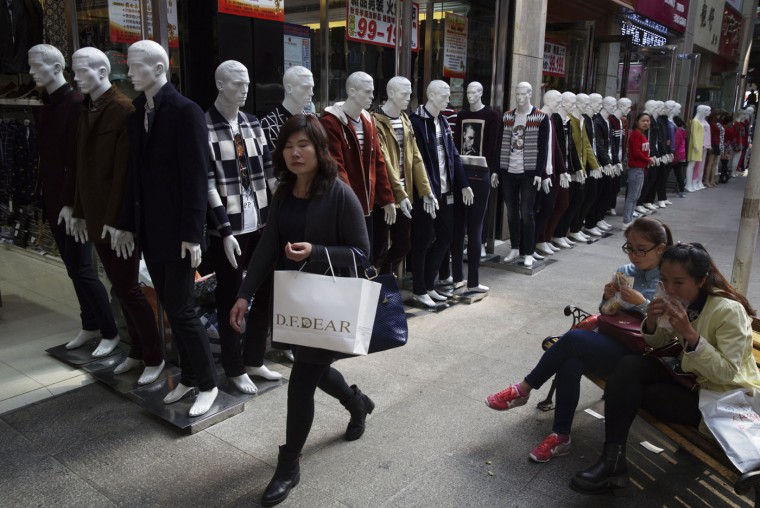 Shoppers walk past a row of mannequins at a shopping mall in Yinchuan in northwestern China's Ningxia Hui autonomous region on Sunday, Oct. 11, 2015. China's leaders have sought to reassure the world that China's economy will continue to expand, despite signs that the country's economic growth appears to be slowing. (AP Photo/Ng Han Guan)