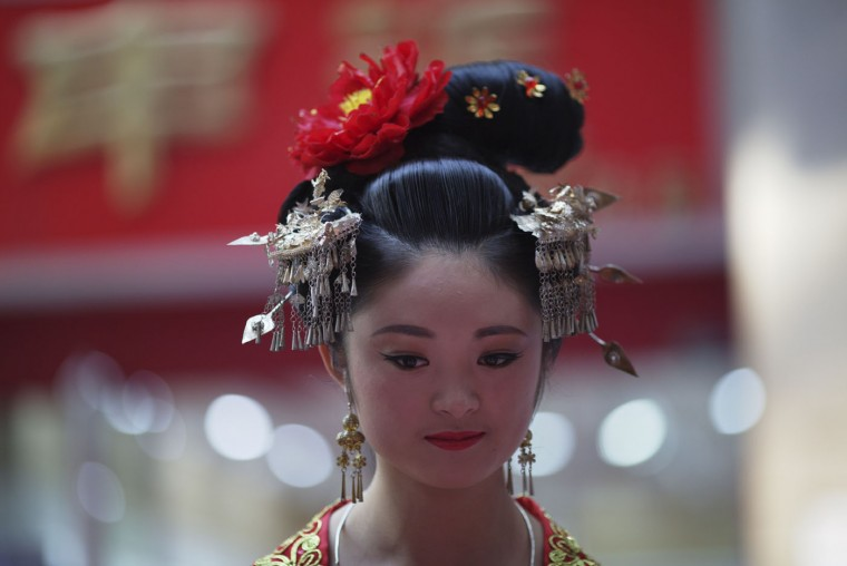 A Chinese model in traditional costumes promotes a photography service at a shopping mall in Yinchuan in northwestern China's Ningxia Hui autonomous region on Sunday, Oct. 11, 2015. China's leaders have sought to reassure the world that China's economy will continue to expand, despite signs that the country's economic growth appears to be slowing. (AP Photo/Ng Han Guan)