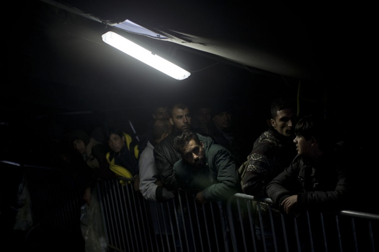 People queue inside a tent in order to be allowed into a registration center for migrants and refugees in Opatovac, Croatia, Tuesday, Oct. 20, 2015. Croatia's interior minister says his country is trying to coordinate the transfer of migrants with Slovenia, which has accused its neighbor of failing to manage the relentless flow of people. (AP Photo/Marko Drobnjakovic)