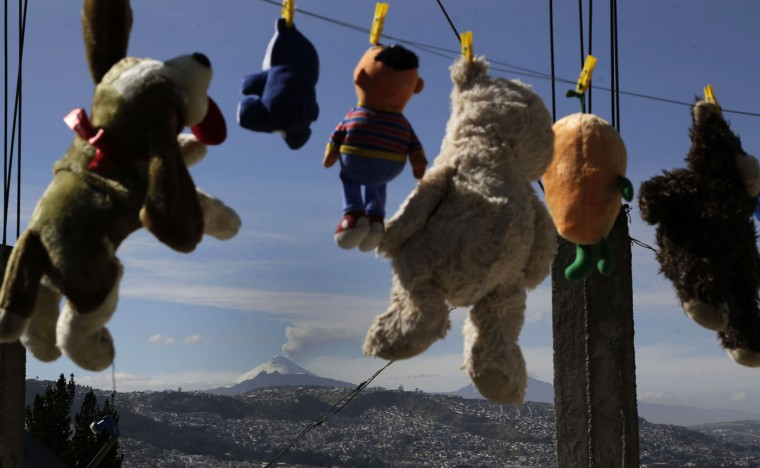 Plush toys hanging from a makeshift clothesline frame a view of the Cotopaxi volcano, in Quito, Ecuador, Thursday, Oct. 8, 2015. Ecuador's restive Cotopaxi has been spewing plumes of ash and gas far above its crater and volcanologists say its activity has been on the upswing. (AP Photo/Dolores Ochoa)