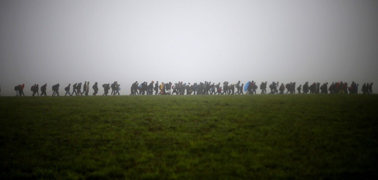 A group of migrants make their way over a meadow after crossing the border between Austria and Germany in Wegscheid near Passau, Germany, Thursday, Oct. 15, 2015. (AP Photo/Matthias Schrader)