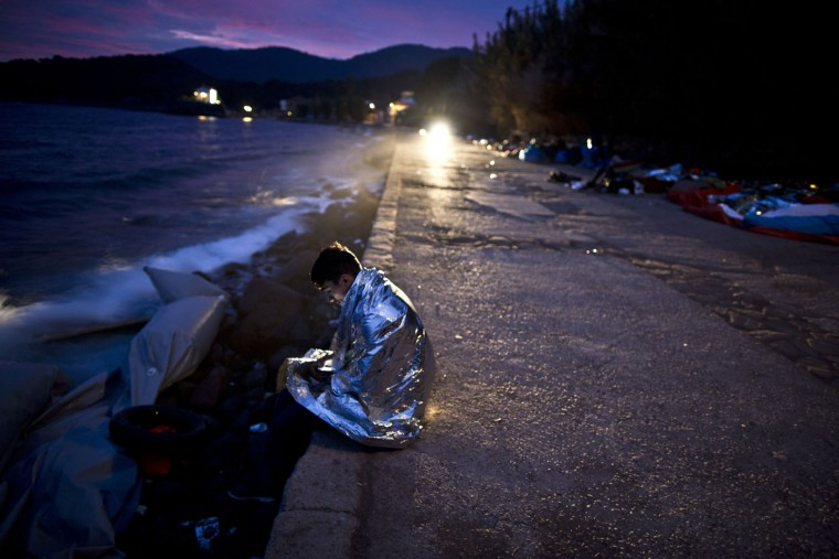 An Afghan refugee wrapped, in a thermal blanket faces the sea after he and others arrived late in the night on a dinghy from the Turkish coast to the northeastern Greek island of Lesbos, early Thursday, Oct. 8 , 2015. More than 500,000 people have arrived in the European Union this year, seeking sanctuary or jobs and sparking the EU's biggest refugee emergency in decades. (AP Photo/Muhammed Muheisen)