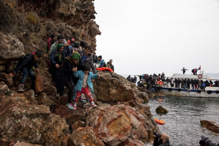 """Migrants try to make their way on rocks after their arrival by boat, on the eastern Aegean island of Lesbos, Greece, Sunday Oct. 11, 2015. Greece's first """"hotspot,"""" or migrant processing center, will open over the next 10 days, allowing migrants to be flown to other European Union countries, mostly of their preference, and have their asylum applications processed there, European Union officials say. (AP Photo/Antonis Pasvantis)"""