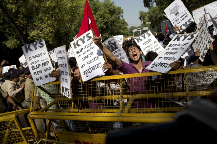 """A Krantikari Yuva Sangathan (KYS) activist shouts slogans during a protest against the killing of a 52-year-old Muslim farmer Mohammad Akhlaq, in New Delhi, India, Sunday, Oct. 11, 2015. A few days ago Indian villagers allegedly beat Akhlaq to death and severely injured his son upon hearing rumors that the family was eating beef, a taboo for many among India's majority Hindu population. The incident happened in Bisara, a village about 45 kilometers (25 miles) southeast of the Indian capital of New Delhi. Placards read, foreground, """"Down with Ministers and Sectarians of India's ruling Bharatiya Janata Party (BJP)"""", left, """"Shame on Mahesh Sharma, a BJP member of parliament, who called the murder as accident"""". (AP Photo /Tsering Topgyal)"""