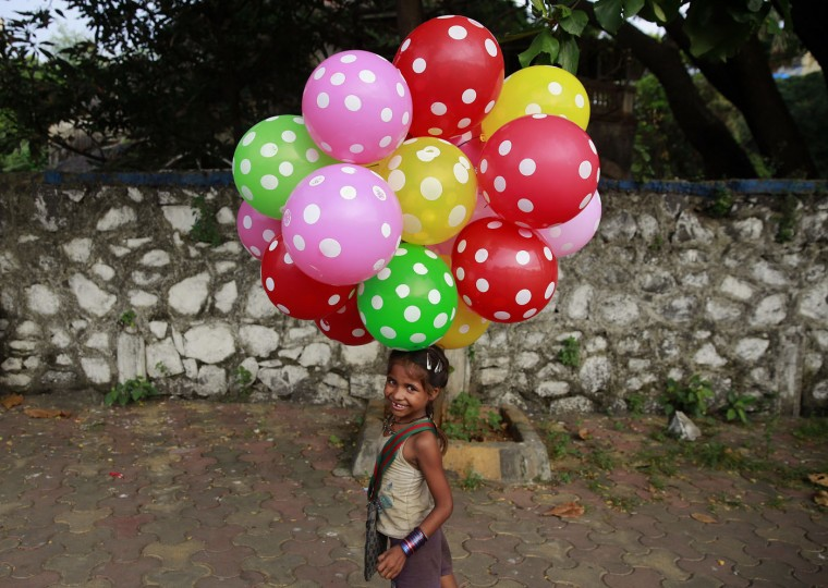 Lali carries balloons to sell on a beach in Mumbai, India, Sunday, Oct. 11, 2015. The United Nations General Assembly marks Oct. 11 as the International Day of the Girl Child, to recognize girls' rights and the unique challenges girls face around the world. (AP Photo/Rafiq Maqbool)