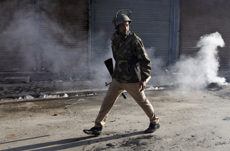 An Indian policeman watches from a distance as Kashmiri Muslim protesters throw stones and bricks at them during a protest in Srinagar, Indian controlled Kashmir, Tuesday, Oct. 20, 2015. Police fired teargas to disperse Kashmiris protesters who protested against the allegedly beating of Yasin Malik, a senior separatist leader. Yasin, along with his supporters were beaten and detained by Indian security personnel when they were going to visit the house of Zahid Rasool, a Muslim teenage truck conductor, who died after he was attacked by a Hindu mob over rumors of cows being slaughtered. (AP Photo/Dar Yasin)