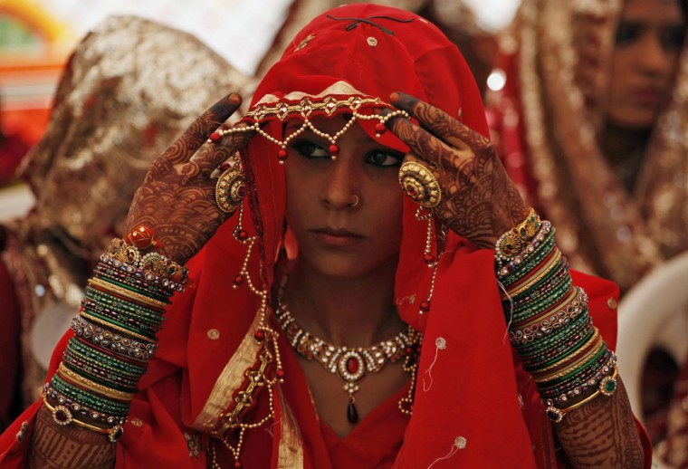 An Indian bride adjusts her veil during a mass marriage ceremony in Ahmadabad, India, Sunday, Oct. 11, 2015. Sixty five Muslim couples tied the knot in a single ceremony organized by a social organization. (AP Photo/Ajit Solanki)