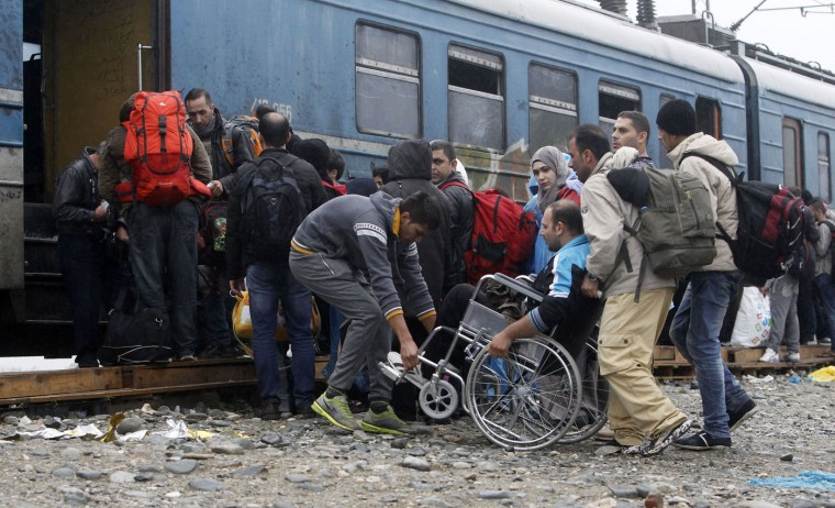 People help a wheelchair user board a train with others, heading towards Serbia, at the transit camp for refugees near the southern Macedonian town of Gevgelija, on Thursday, Oct. 8, 2015. Several thousand migrants and refugees enter daily from Greece into Macedonia on their way through the Balkans towards the more prosperous European Union countries. More than 500,000 people have arrived this year in EU seeking sanctuary or jobs, sparking the EU's biggest refugee emergency in decades. (AP Photo/Boris Grdanoski)