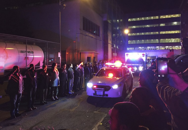 Police salute outside Harlem Hospital Center as the body of New York Police Department Officer Randolph Holder passes by in an ambulance, early Wednesday, Oc. 21, 2015, in New York. Holder, 33, died after being shot in the head in a gun battle Tuesday while pursuing a suspect following a report of shots fired, police said. (AP Photo/Michael Balsamo)