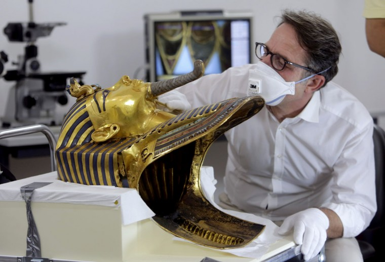 German restorer Christian Eckmann examines the beard of the golden mask of the famed King Tutankhamun as an Egyptian-German team begins restoration work over a year after the beard was accidentally broken off and hastily glued back with epoxy, at the Egyptian Museum in Cairo, Egypt, Tuesday, Oct. 20, 2015. The 3,300-year-old burial pharaonic mask was discovered in Tutankhamun's tomb along with other artifacts by British archeologists in 1922, sparking worldwide interest in archaeology and ancient Egypt. (AP Photo/Amr Nabil)