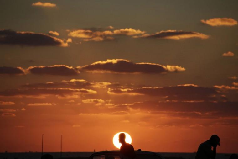 The sun sets as Egyptians walk on the beach of Alexandria, Egypt, Wednesday, Oct. 14, 2015. (AP Photo/Amr Nabil)