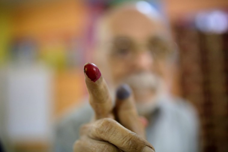 Egyptian voter Abdel Moneam Kandil, 80, shows his inked finger after he voted at a polling station of the runoff to the first round of the parliamentary elections in Giza, just outside of Cairo, Egypt, Wednesday, Oct. 28, 2015. (AP Photo/Amr Nabil)