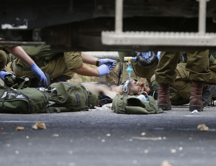 "Israeli soldiers treat Palestinians wounded during clashes between Palestinians and Israeli military forces, near Ramallah, West Bank, Wednesday, Oct. 7, 2015. Israel's prime minister says he is calling off a planned trip to Germany because of a wave of violence between Israelis and Palestinians. A statement from Benjamin Netanyahu's office Wednesday said the Israeli leader would not depart for the two-day visit so that he could ""closely monitor the situation."" (AP Photo/Majdi Mohammed)"