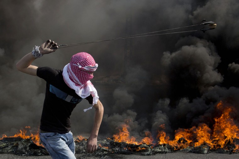 A Palestinian swings a sling during clashes with Israeli troops, near Ramallah, West Bank, Tuesday, Oct. 20, 2015. U.N. Secretary-General Ban Ki-moon called for calm during a surprise visit to Jerusalem on Tuesday ahead of meetings with Israeli and Palestinian leaders, in a high-profile gambit to bring an end to a monthlong wave of violence.(AP Photo/Majdi Mohammed)
