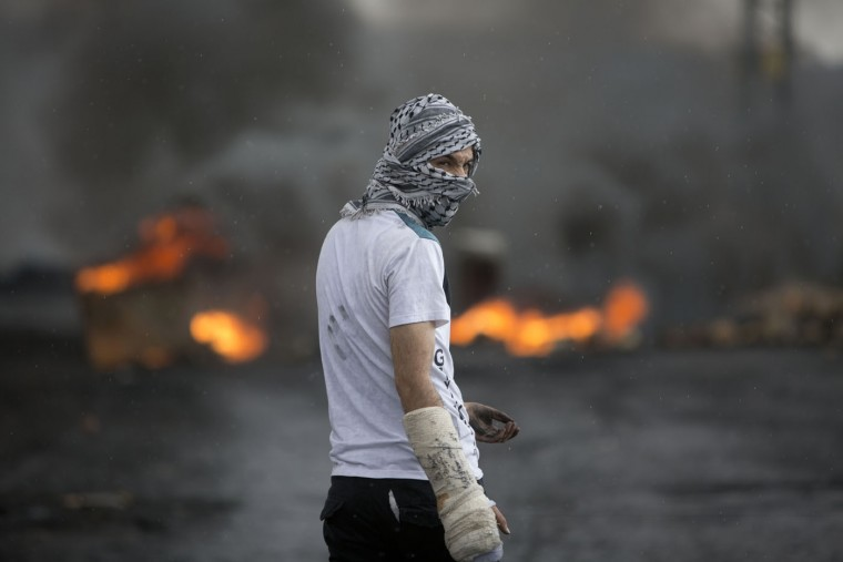 A masked Palestinian protester stands amid smoke of burning tires during clashes with Israeli troops near Ramallah, West Bank, Thursday, Oct. 8, 2015. (AP Photo/Majdi Mohammed)
