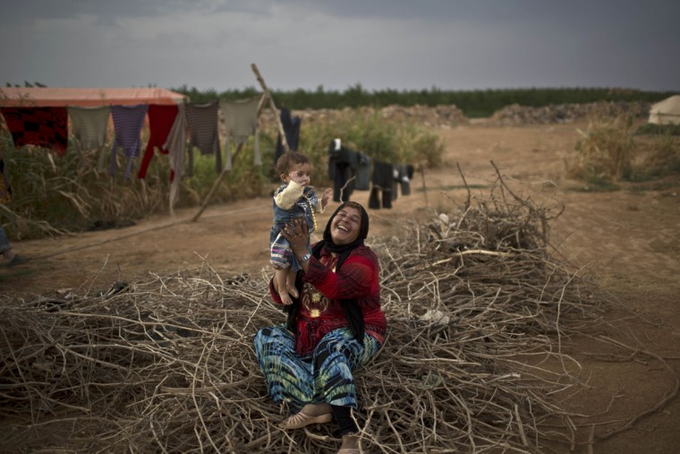 Syrian refugee Fatima Jassim, 40, plays with her 7-month-old daughter Marwa while sitting on a pile of wood to be used for cooking, outside their tent at an informal tented settlement near the Syrian border on the outskirts of Mafraq, Jordan, Monday, Oct. 19, 2015. (AP Photo/Muhammed Muheisen)