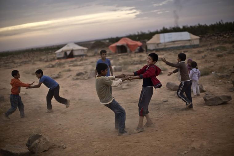 Syrian refugee boys play in an informal tented settlement near the Syrian border on the outskirts of Mafraq, Jordan, Friday, Oct. 23, 2015. (AP Photo/Muhammed Muheisen)