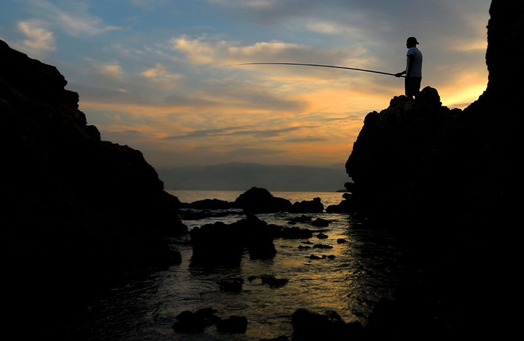 A Lebanese angler casts his fishing pole from a rocky coastal area along the Beirut coastline as the sun rises over the Mediterranean Sea, Lebanon, Tuesday, Oct. 6, 2015. (AP Photo/Hassan Ammar)