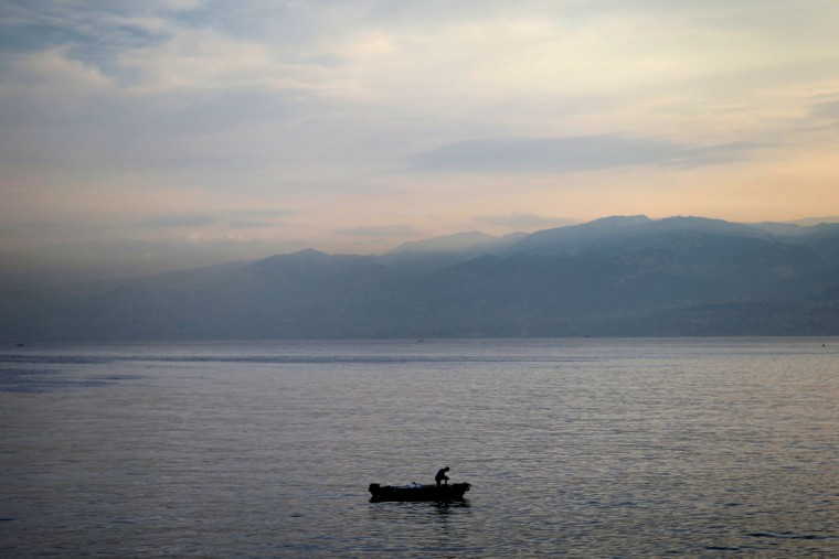 A Lebanese man fishes along the Beirut coastline, as the sun rises over the Mediterranean Sea, Lebanon, Tuesday, Oct. 6, 2015. (AP Photo/Hassan Ammar)