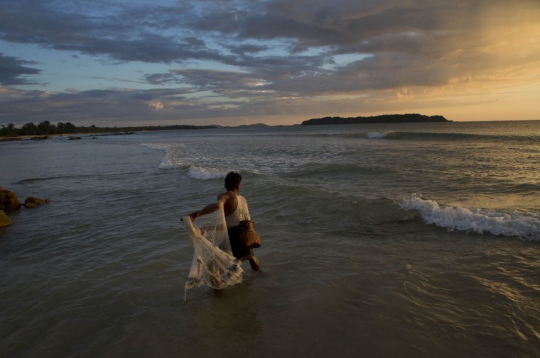 A fisherman throws a net to catch fish in the shallow waters of Ngapali beach in Myanmar's western Rakhine State at dusk, Thursday, Oct. 15, 2015. Myanmar's general elections are scheduled for Nov. 8, the first since a nominally civilian government was installed in 2011. (AP Photo/Gemunu Amarasinghe)