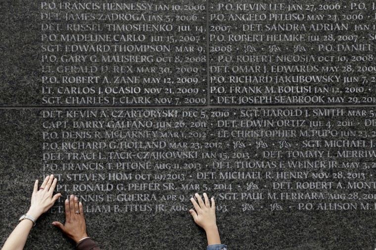 Family members of police officers who died in the line of duty touch the names of their loved ones during a rededication ceremony at the Police Memorial Wall in Battery Park, Tuesday, Oct. 13, 2015, in New York. Every year the New York Police Department holds a ceremony to honor officers who died in the line of duty in the past year. (AP Photo/Mary Altaffer)