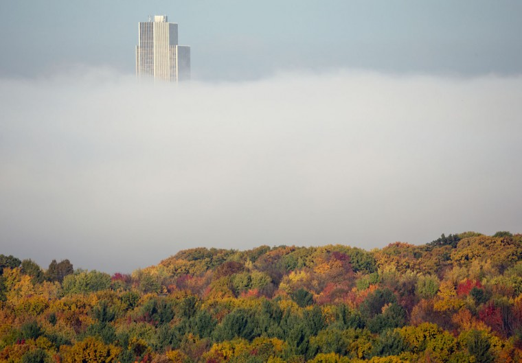 The Corning Tower at the Empire State Plaza in Albany is shrouded in autumn colors and morning fog from the Hudson River as seen from East Greenbush, N.Y., on Tuesday, Oct. 27, 2015. (AP Photo/Mike Groll)