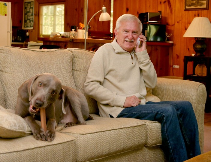 Paul Modrich takes a phone call as he sits on the couch with his dog Dover at his vacation home in Rumney, N.H., Wednesday, Oct. 7, 2015. Modrich, an investigator at Howard Hughes Medical Institute and professor at Duke University School of Medicine in Durham, N.C., is one of three scientists who won the Nobel Prize in chemistry on Wednesday for showing how cells repair damaged DNA, work that has inspired the development of new cancer treatments. (AP Photo/Mary Schwalm)