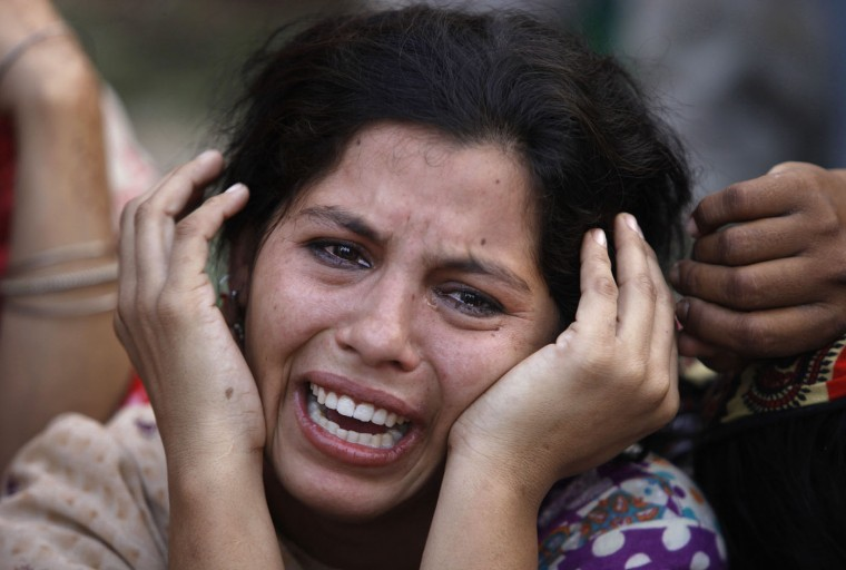 A woman mourns the death of her daughter, a victim of landslide, in Karachi, Pakistan, Tuesday, Oct. 13, 2015. Police say a landslide has hit three makeshift homes in a slum, killing more than a dozen people. Senior police officer Javed Jaskani says the incident took place early Tuesday when a mass of mud and rocks crashed down a hill into camps in Karachi, the capital of southern Sindh province. He says women and children were among the dead and injured. (AP Photo/Shakil Adil)