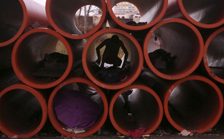 A Filipino man prepares his sleeping area inside a huge water pipe while others sleep in other pipes in suburban Pasay, south of Manila, Philippines Tuesday, Oct. 20, 2015. Several homeless people have made the pipes as their temporary shelter. (AP Photo/Aaron Favila)