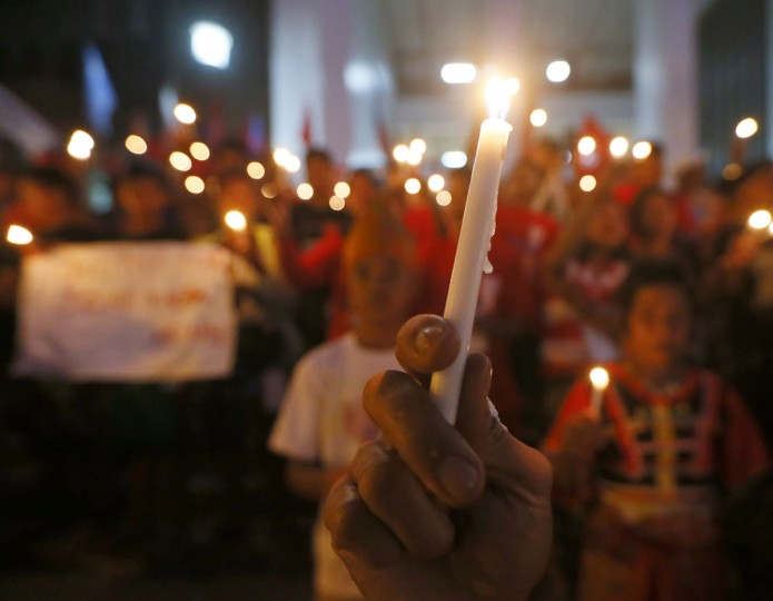 "Students and indigenous peoples collectively known as ""Lumads"" hold lighted candles following their march around the University of the Philippines campus to denounce the recent killings of their leaders in southern Philippines Wednesday, Oct. 28, 2015 in suburban Quezon city, northeast of Manila, Philippines. The ""Lumads,"" who traveled to Manila by land and sea, are demanding the pullout of government forces as well as disband paramilitary groups from their ancestral lands in the south. (AP Photo/Bullit Marquez)"